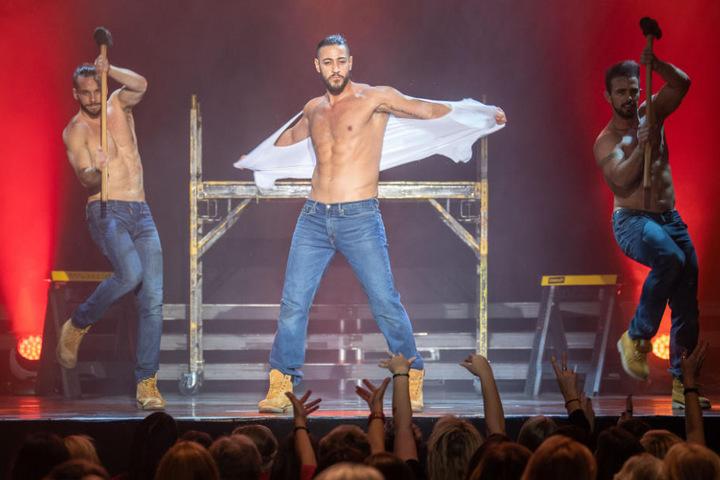 Ein Darsteller der Chippendales reißt sich bei seiner Choreografie auf der Tanzfläche das T-Shirt vom Leib.