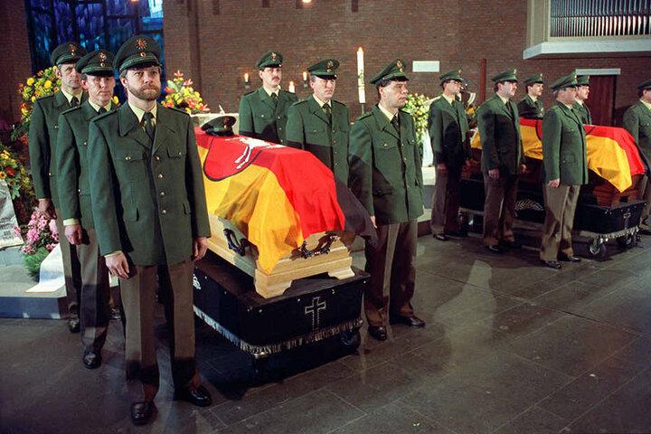 Am 24. Oktober 1991 halten Beamte der Polizeiwache Totenwache an den mit Flaggen bedeckten Särgen.