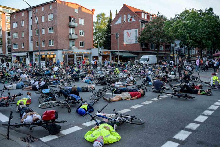 Hunderte Radfahrer sitzen oder liegen auf der Kreuzung von Eppendorfer Weg und Osterstraße, um der tödlich verunglückten Radfahrerin zu gedenken.