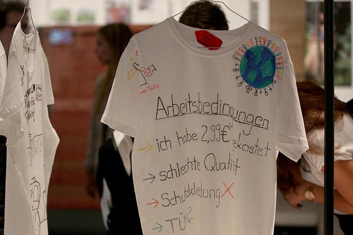 Auf einem T-Shirt werden die Produktionsbedingungen und die Preispolitik bei Billigtextilien angeprangert.