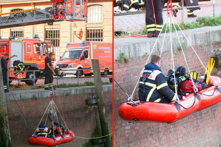 Die Feuerwehr lässt mithilfe eines Leiterwagens ein Rettungsboot mit Tauchern ins Wasser.