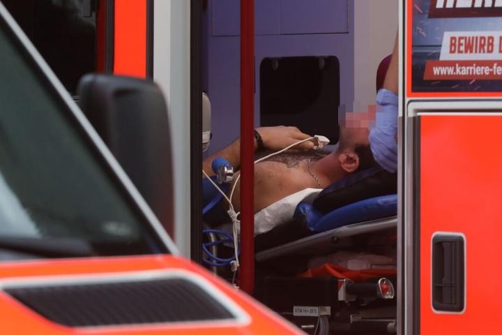 Ein Mann wird von den Sanitätern im Rettungswagen versorgt.