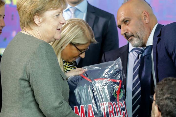 Bundeskanzlerin Angela Merkel erhält von Bürgermeister Sergio Pirozzi einen Kapuzenpulli.