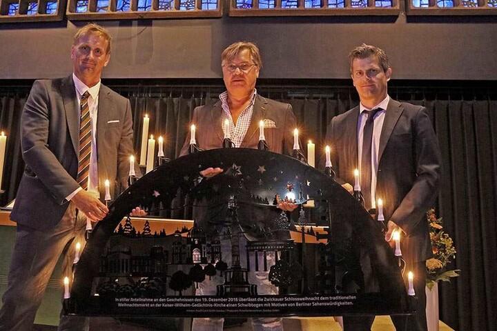 Rene Groh (39, l.) hat den Schwibbogen auf Initiative der Macher der Schlossweihnacht wie Jörg Hempel (42, r.) hergestellt und an die Organisatoren des Berliner Weihnachtsmarktes wie Michael Roden (55) übergeben.