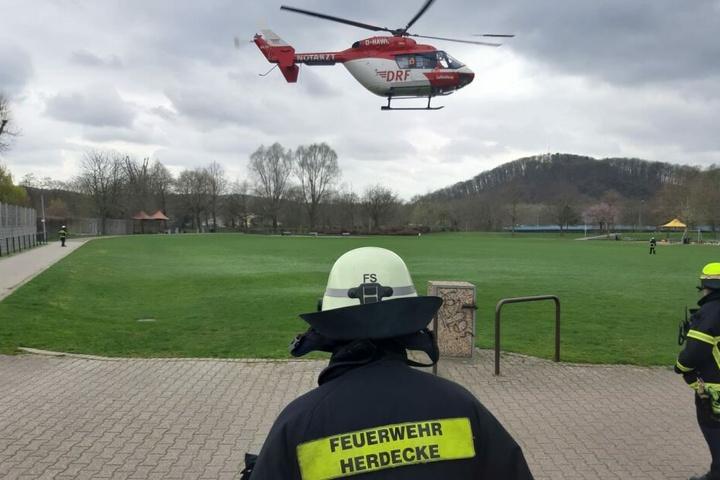 Feuerwehrleute beobachten den Start des Hubschraubers.