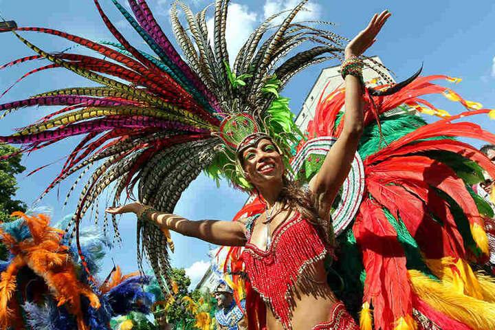 Bei strahlendem Sonnenschein tanzt eine kostümierte Tänzerin einer Samba-Schule am 27.05.2012 während des Karnevals der Kulturen.