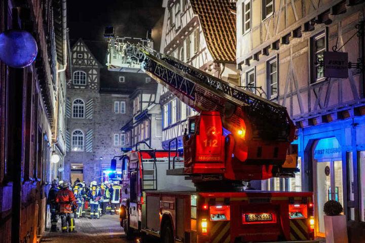 Mit einer Drehleiter löschen die Feuerwehrleute das Fachwerkhaus.