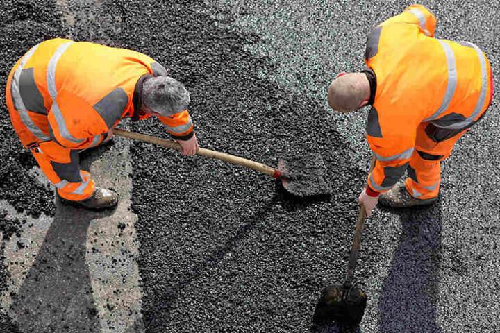 Zwei Straßenbauer flicken ein Schlagloch mit dem Kaltasphalt.