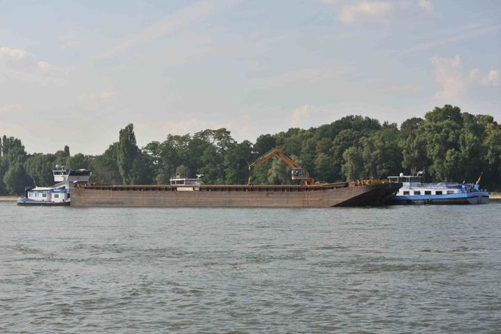 Mehrere Bergeschiffe entladen das havarierte Schiff auf dem Rhein in Köln-Rodenkirchen.