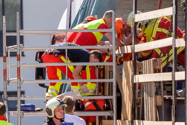 Rettungskräfte befreien den eingeklemmten Bauarbeiter.