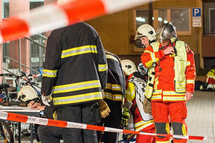 Einsatzkräfte der Feuerwehr werten die im Hausflur genommenen Proben aus.