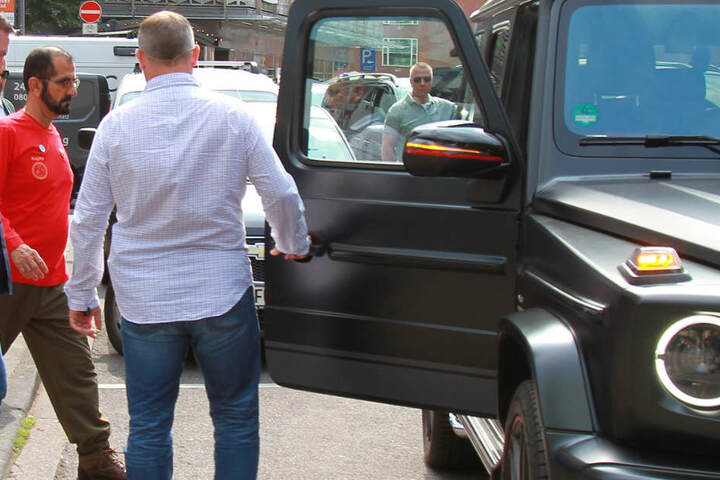 Unter Schutz der Leibwächter steigt der Emir von Dubai nach dem Besuch in Köln wieder in den Mercedes G AMG.