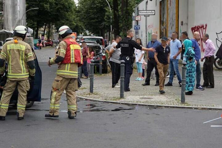 Ein Polizist versucht die Gaffer von der Unfallstelle fernzuhalten.