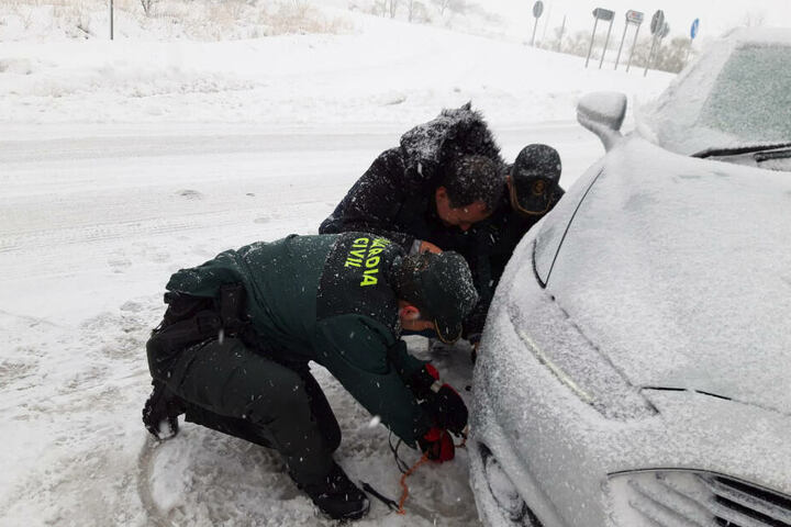 Zwei Beamte der Guardia Civil helfen einem Fahrer in Carinena beim Anlegen der Schneeketten.