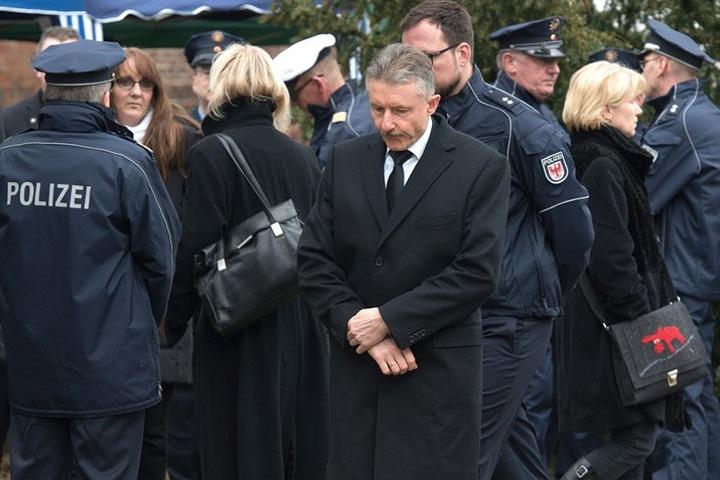 Innenminister Karl-Heinz Schröter (M, SPD) auf der Beerdigung eines der zwei überfahrenen Polizisten.