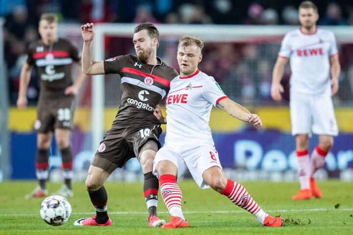 St. Paulis Christopher Buchtmann (l) und Kölns Johannes Geis im Kampf um den Ball.