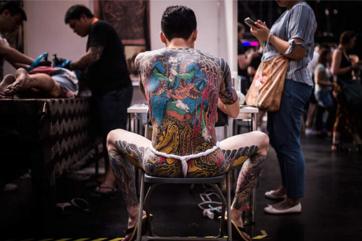 Ein Mann glänzt mit seinem Ganzkörper-Tattoo in der Arena Treptow.