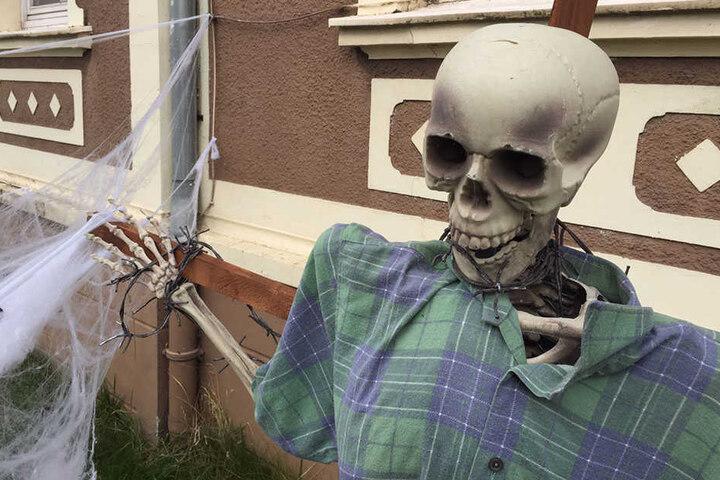 Vor dem Haus steht eine Skelett-Figur mit Stacheldraht um den Hals.