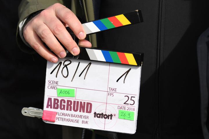 Ein Kameraassistent hält eine Filmklappe in seiner Hand.