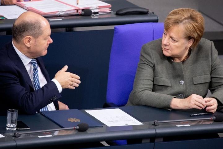 Olaf Scholz sitzt im Bundestag neben der Kanzlerin Angela Merkel. Beide sind aktuell in Argentinien.