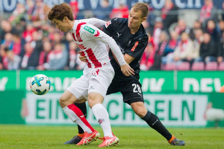Kölns Yuya Osako (l.) und Stuttgarts Holger Badstuber versuchen an den Ball zu kommen.