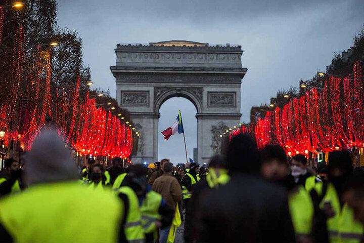Demonstranten stehen vor dem Arc de Triomphe.