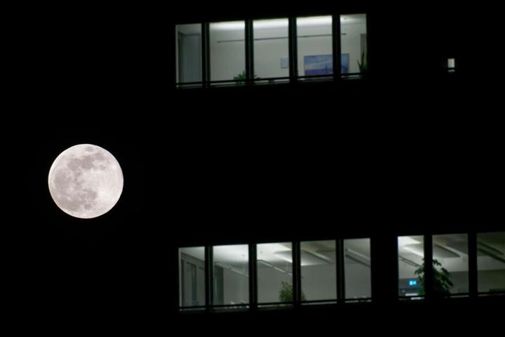 Auch in Köln: Der Vollmond leuchtet am Abendhimmel neben einem Bürogebäude.