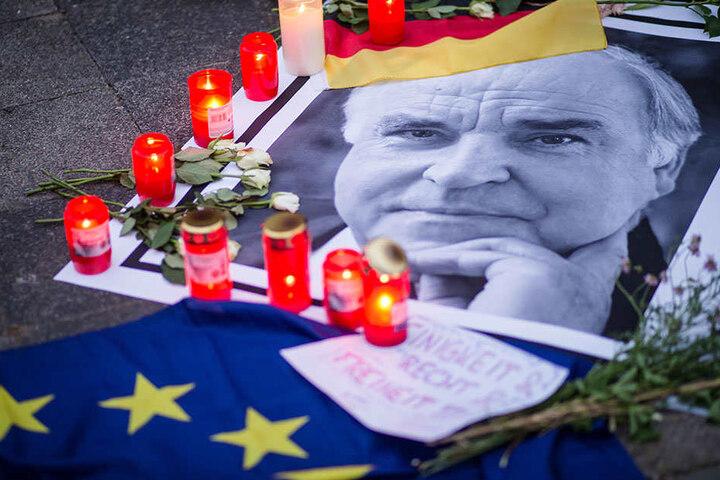 Trauerkerzen stehen in den frühen Morgenstunden am Haus des früheren Bundeskanzlers Helmut Kohl in Ludwigshafen-Oggersheim neben einem Bild von ihm.