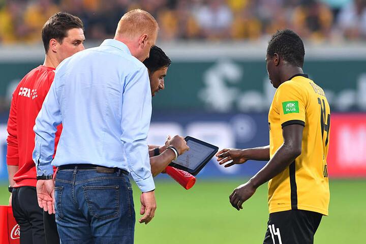 Moussa Koné (r.) bekommt kurz vor seiner Einwechslung von Co-Trainer Ovid Hajou (hint.) per Tablet letzte Hinweise.
