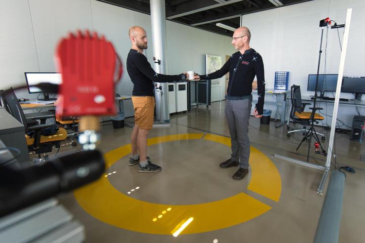 Roboter lernen über die Marker, wie sie eine Tasse übergeben müssen.