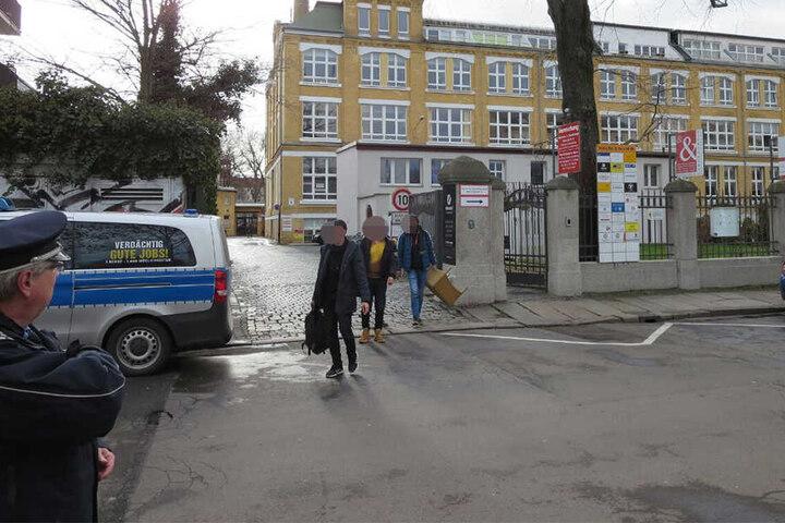 Schüler verlassen unter polizeilicher Aufsicht das Schulgebäude.