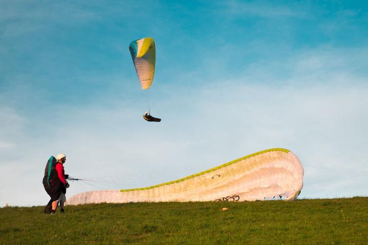 Auf einer Wiese ist ein Fallschirmspringer gelandet, ein weiterer setzt zur Landung an. (Symbolbild)