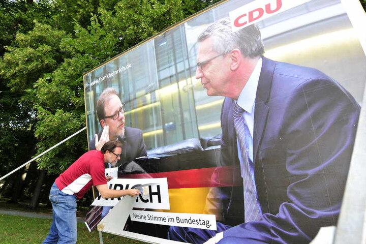 Frank Heinrich (CDU) versuchtdas Plakat an der Hartmannstrasse notdürftig zu reparieren