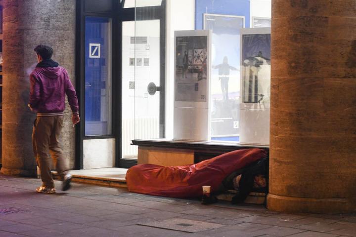 Ein Obdachloser in Köln schläft bei Minusgraden vor einer Bankfiliale.