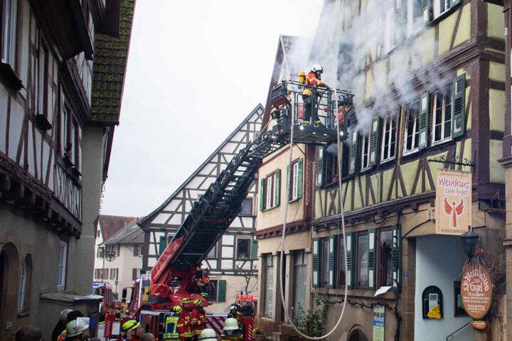 Feuerwehrleute stehen vor dem brennenden Fachwerkhaus in Neudenau.
