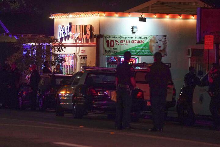 Polizisten stehen nahe des Tatorts der Schießerei, die in einem Hinterhof eines Hauses hinter einem Nagelsalon stattgefunden hatte.