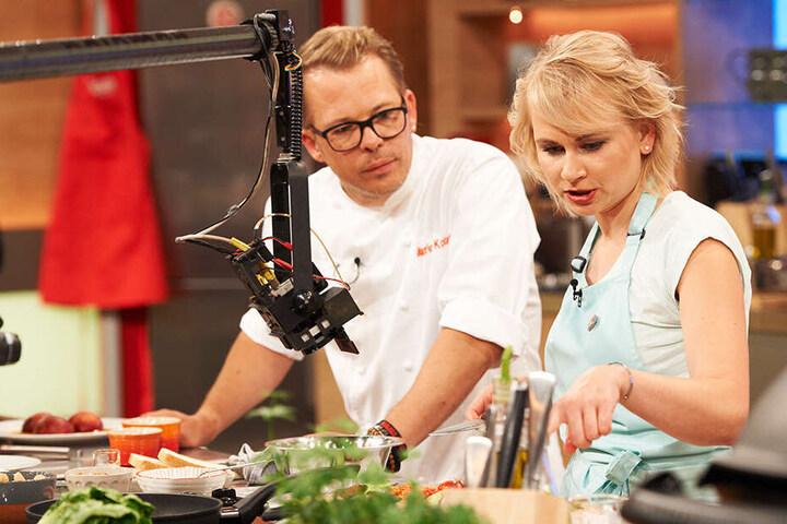 """Profikoch Mario Kotaska (45) moderiert die aktuelle Ausgabe der """"Küchenschlacht"""" und schaut Lubina beim Kochen über die Schulter."""