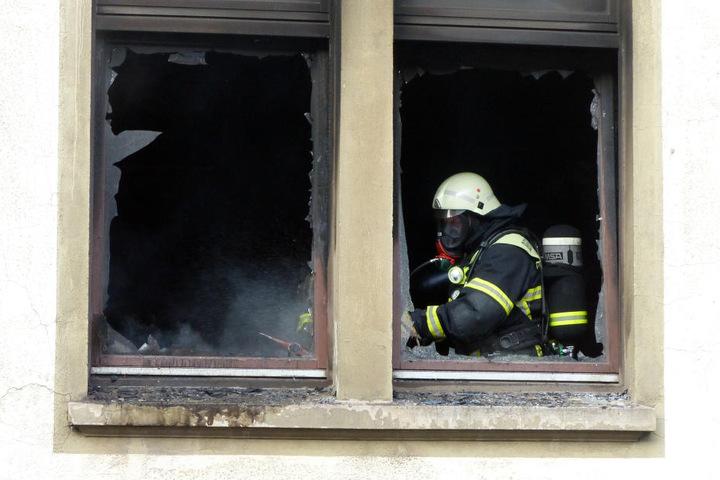 Ein Feuerwehrmann löscht am 14.09.2016 in Nordhausen (Thüringen) einen Brand in einem Mehrfamilienhaus.