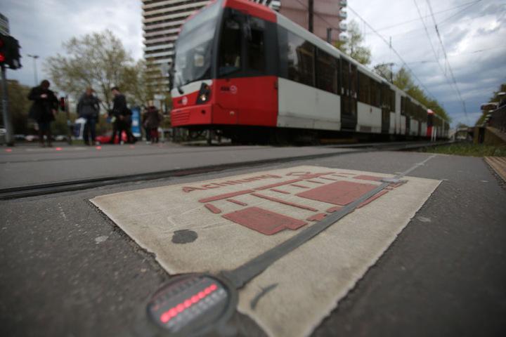 Piktogramme und Lämpchen im Asphalt warnen Kölner vor der Straßenbahn.