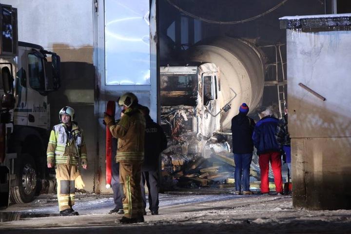 Im Hintergrund ist einer der abgebrannten Betonmischer zu sehen.