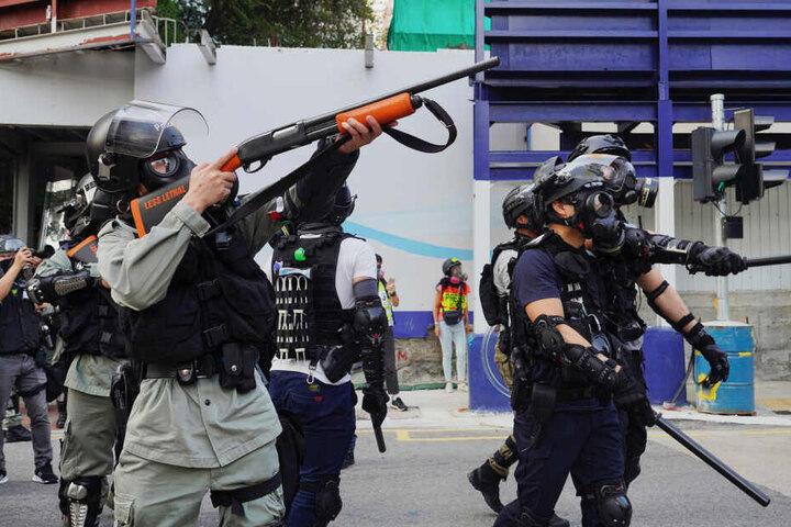 Ein Polizist richtet seine Waffe auf Demonstranten während eines Zusammenstoß bei einer Kundgebung gegen Polizeigewalt. (Archivbild)