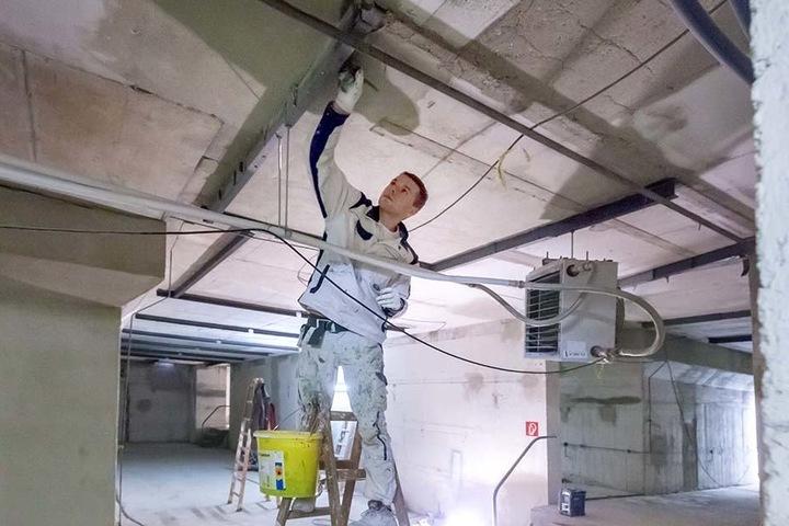 Marco Pohler (21) streicht Stahlträger im Keller des Gablenzer Bades mit  Rostschutzfarbe.