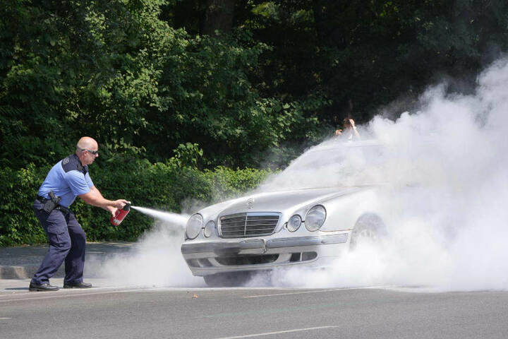 Ein Polizist muss den brennenden Wagen löschen.