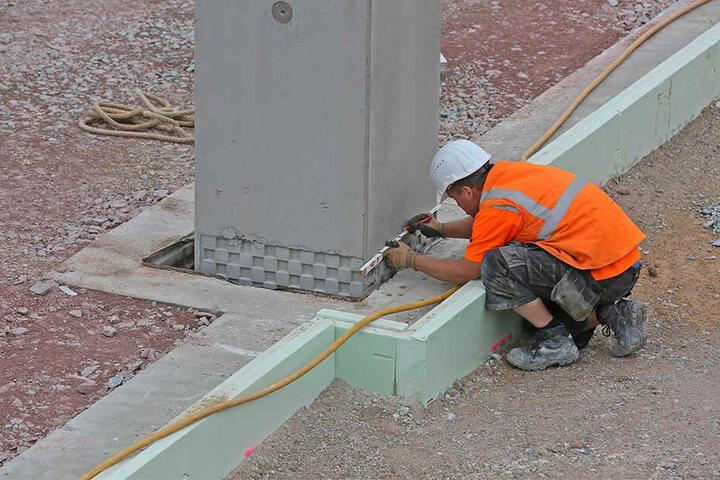 Ein Bauarbeiter prüft eine Säule für die neue Logistikhalle