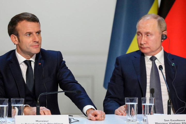 Emmanuel Macron (l), Präsident von Frankreich, und Wladimir Putin, Präsident von Russland, sitzen auf zu gemeinsamen Pressekonferenz im Pariser Schloss Elysee.