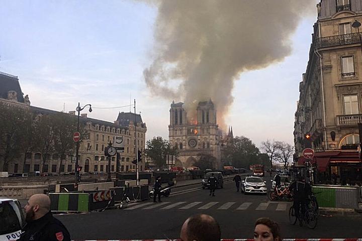 Eine Straße ist abgesperrt, während im Hintergrund Rauch von der Kathedrale Notre-Dame aufsteigt.