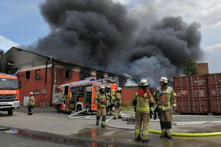 Feuerwehrleute stehen vor der Lagerhalle.