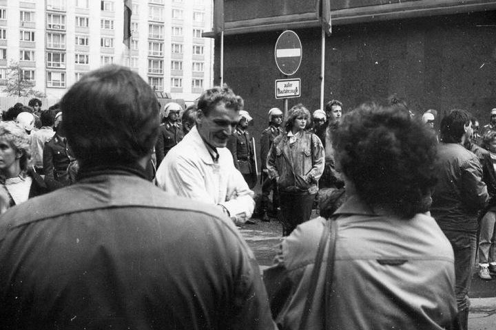Polizisten mit Helm, Schild und Gummiknüppel haben den Nikolaikirchhof abgeriegelt, dennoch versammeln sich Hunderte Menschen zum Protest.