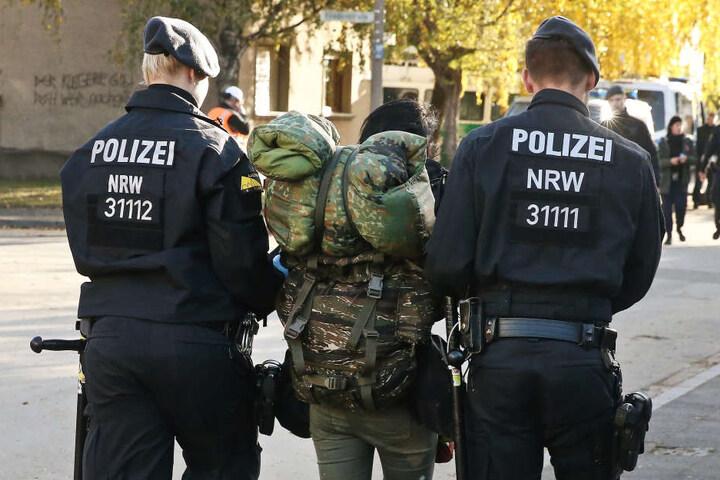 Polizisten führen im Stadtteil Manheim einen Aktivisten ab.