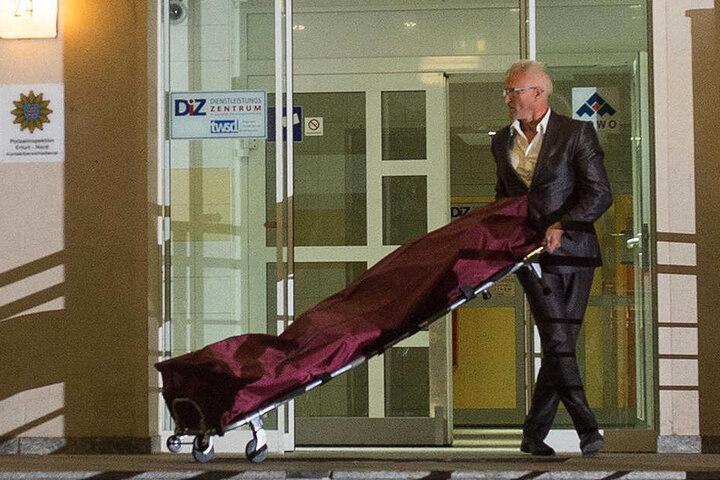 Ein Bestatter bringt die Leiche der 48-Jährigen aus dem Gebäude.
